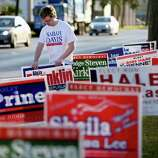 Evan Lee, campaign manager for Sarah Davis, places yard signs at the Metropolitan Multi Service Center on West Gray on Monday, October 20, 2014 in Houston, Texas.