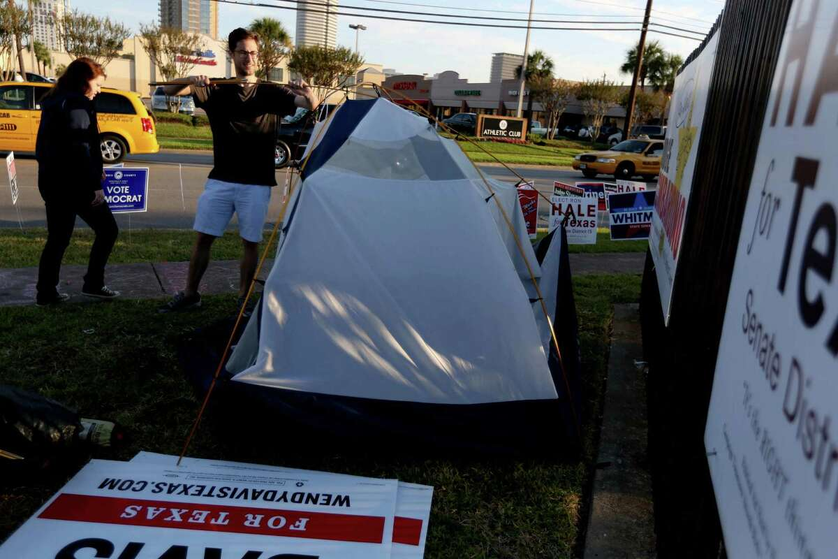 Volunteer William Montgomery breaks down a tent where he slept to help the campaign of gubernatorial candidate Wendy Davis at early voting at State Representative District 134M at the Metropolitan Multi Service Center on West Gray.