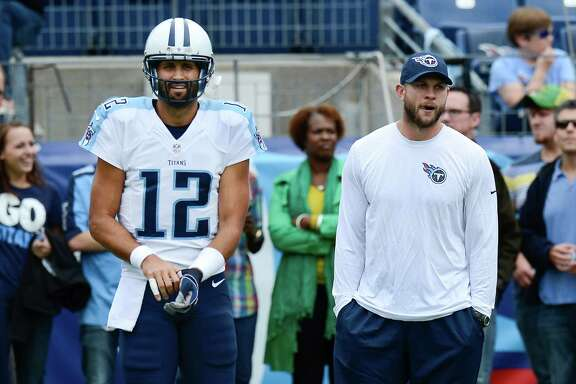 Injured Tennessee Titans quarterback Jake Locker, right, stands with quarterback Charlie Whitehurst (12) before an NFL football game between the Titans and the Jacksonville Jaguars Sunday, Oct. 12, 2014, in Nashville, Tenn. (AP Photo/Mark Zaleski)