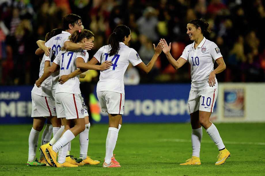 Teammates congregate toward Carli Lloyd, right, whose goal in the ninth minute opened the scoring for the U.S. women as they eliminated Haiti from World Cup qualifying. The U.S. women are unbeaten in 90 games (79-0-11) at home. Photo: Patrick McDermott, Stringer / 2014 Getty Images