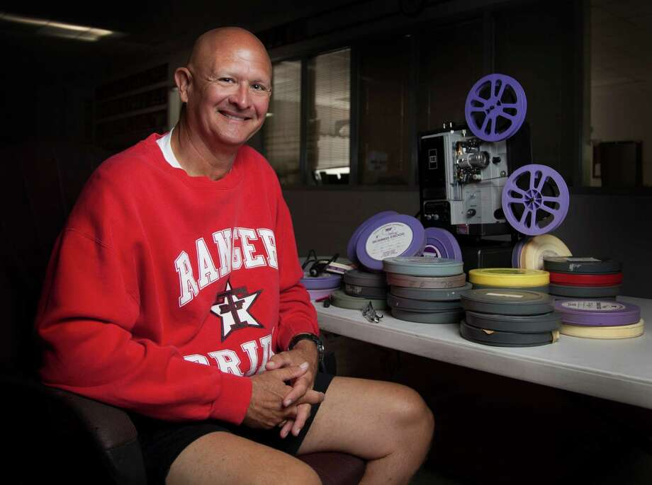 Like an old sidekick, a 16-mm film projector has been a constant companion for Terry coach Tim Teykl, who uses it to extol the virtues of option formations used by teams of a bygone era. Tekyl has about 250 canisters of film. Photo: Bob Levey, Photographer / ©2014 Bob Levey
