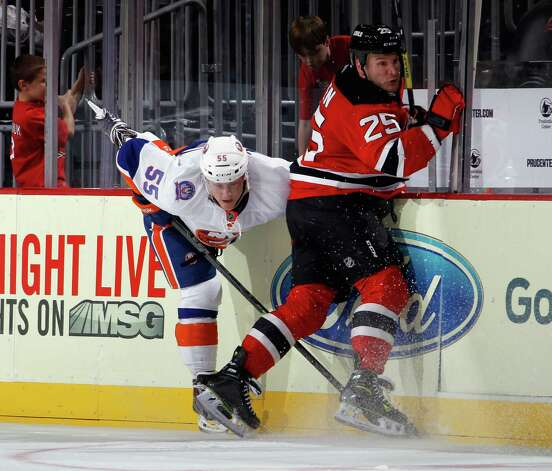 NEWARK, NJ - OCTOBER 02: Cam Janssen #25 of the New Jersey Devils hits Aaron Ness #55 of the New York Islanders during the third period at the Prudential Center on October 2, 2014 in Newark, New Jersey. The Devils defeated the Islanders 2-1 in the shootout. (Photo by Bruce Bennett/Getty Images) ORG XMIT: 508222283 Photo: Bruce Bennett / 2014 Getty Images