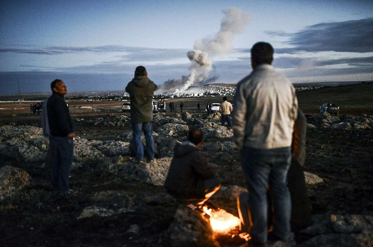 TOPSHOTS Kurdish people observe smoke rising from the Syrian town of Kobane, also known as Ain al-Arab, following an explosion as seen from the southeastern Turkish village of Mursitpinar in the Sanliurfa province on October 20, 2014. US President Barack Obama called his Turkish counterpart Recep Tayyip Erdogan and they pledged to step up the fight against the Islamic State group in Syria, the White House said. Kurdish fighters have been under IS assault for more than a month around Kobane, which has become a key prize as it is being fought under the gaze of the world's press massed just over the border in Turkey. AFP PHOTO / BULENT KILICBULENT KILIC/AFP/Getty Images