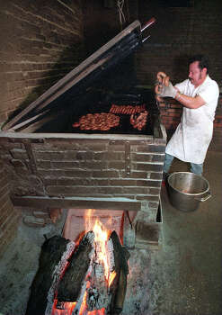 STATE DESK Cook Pablo Garcia puts some sausage on the pit that has a 43 foot chimney that sucks the heat and smoke through the pit to cook the food at Kreuz Market. The Bar Be Que is is in a brother and sister feud in Lockhart... cb Kreuz BBQ 981899 Photo: CHARLES BARKSDALE, File / SAN ANTONIO EXPRESS-NEWS