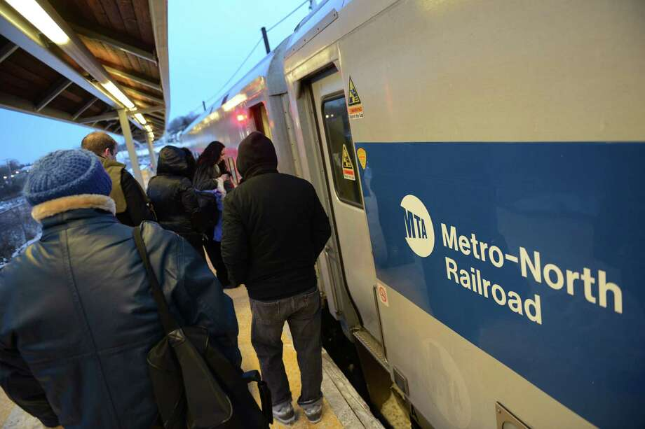 Commuters board the train bound for South Norwalk at the Metro-North train station in Danbury earlier this year. The railroad is piloting a new program on the Danbury line that will allow commuters to use their credit cards to purchase tickets while on board the trains. Photo: Tyler Sizemore / The News-Times