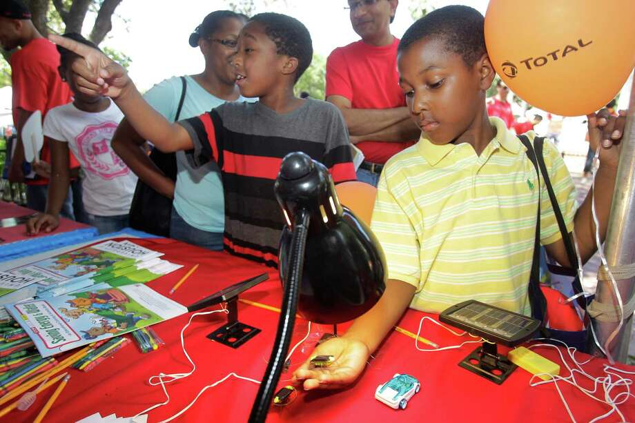 Ba'Cory Batiste, 10, left, and Jadyne Washington, 9, right, check out the solar energy display at the University of Houston booth during the Energy Day Festival over the weekend. Photo: Melissa Phillip, Staff / © 2014  Houston Chronicle