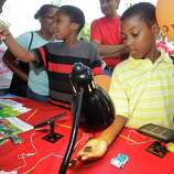 Ba'Cory Batiste, 10, left, and Jadyne Washington, 9, right, check out the solar energy display at the University of Houston booth during the Energy Day Festival over the weekend.