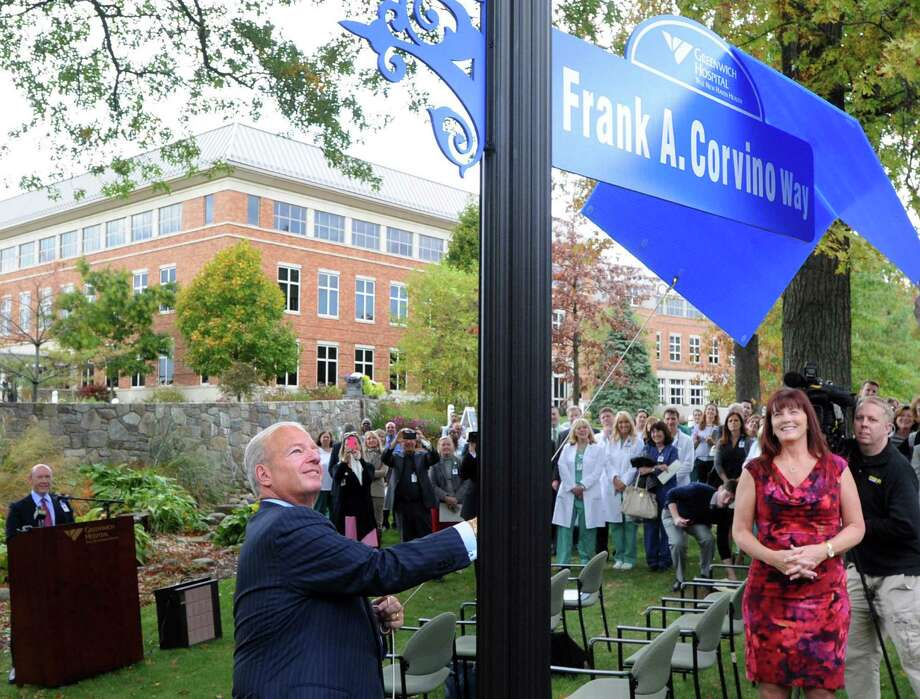 "Greenwich Hospital President and CEO, Frank Corvino, at left, helps to unveil the street sign ""Frank A. Corvino Way,"" during a retirement ceremony for Corvino at the hospital in Greenwich, Conn., Tuesday, Oct. 21, 2014. Photo: Bob Luckey / Greenwich Time"