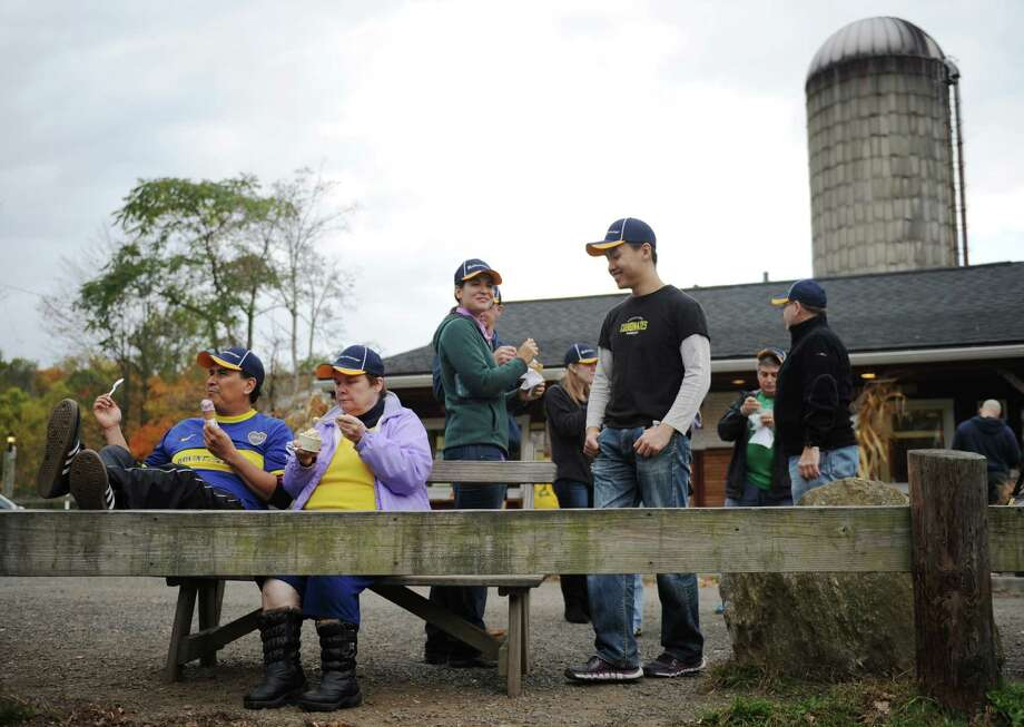 Guillermo Julca, far left, of Fairfield, Claire Ganz, left, of Mount Kisco, N.Y., and others from The Marketing Advantage in Stamford enjoy ice cream during a team building activity at Ferris Acres Creamery in Newtown, Conn. Tuesday, Oct. 21, 2014.  Ferris Acres closes for the season on Thursday, Oct. 30 with a Halloween party from 11:30 a.m. to 9 p.m. Photo: Tyler Sizemore / The News-Times