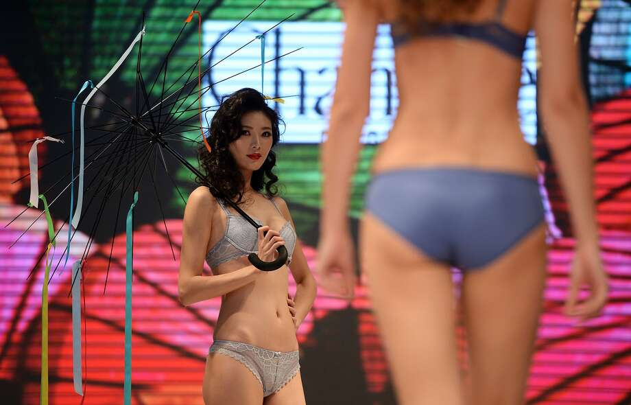 JUST FYI, THAT UMBRELLA IS TOTALLY USELESS: Models present lingerie by Chanelle at the Interfilerie Exhibition during Shanghai Fashion Week. Photo: Johannes Eisele, AFP/Getty Images