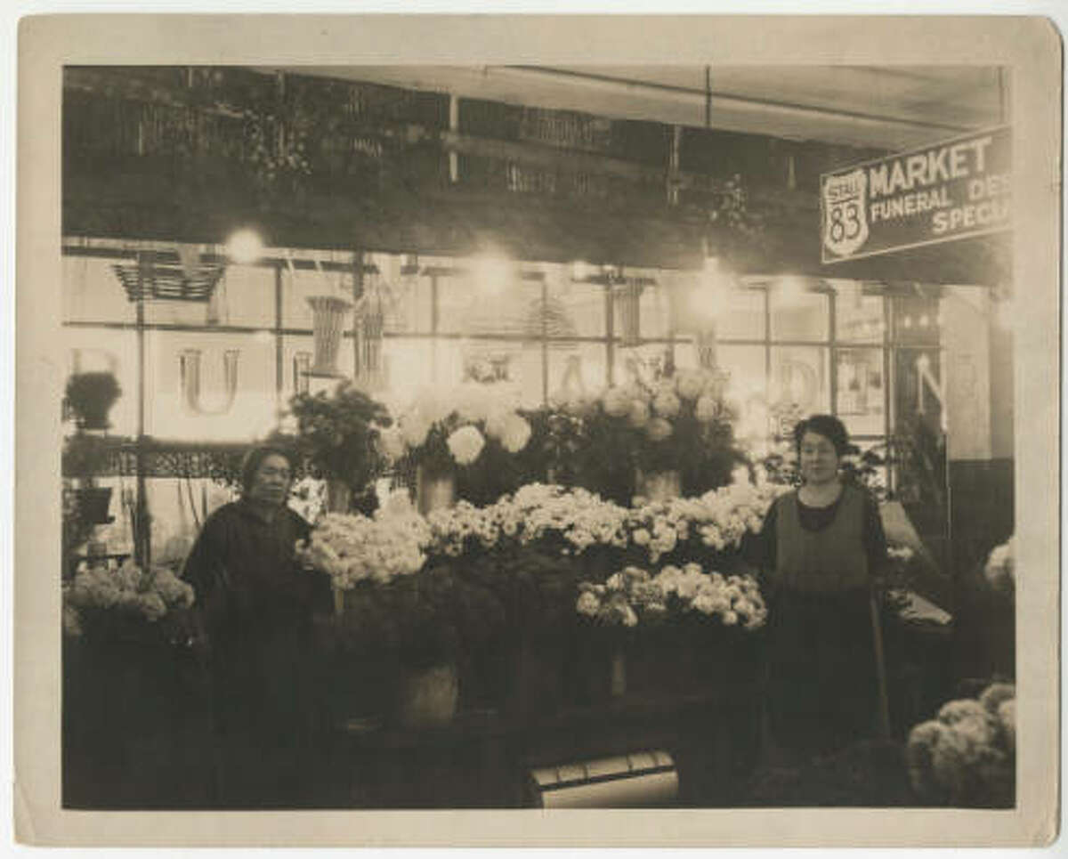 Two women standing before their flower stall at Pike Place Market. Baskets hang in the background. Date unknown, estimated between 1910 and 1931. spl_sh_00007