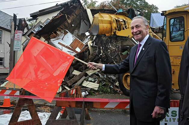 Sen. Charles Schumer waves the orange flag as he joins Schenectady city officials for the demolition of 2033 Broadway, the first of about 89 run-down homes in the municipality on Tuesday, Oct. 21, 2014 in Schenectady, N.Y. Schumer helped the city get about $3 million to help with the cost of knocking down these structures. (Lori Van Buren / Times Union) Photo: Lori Van Buren / 00029128A