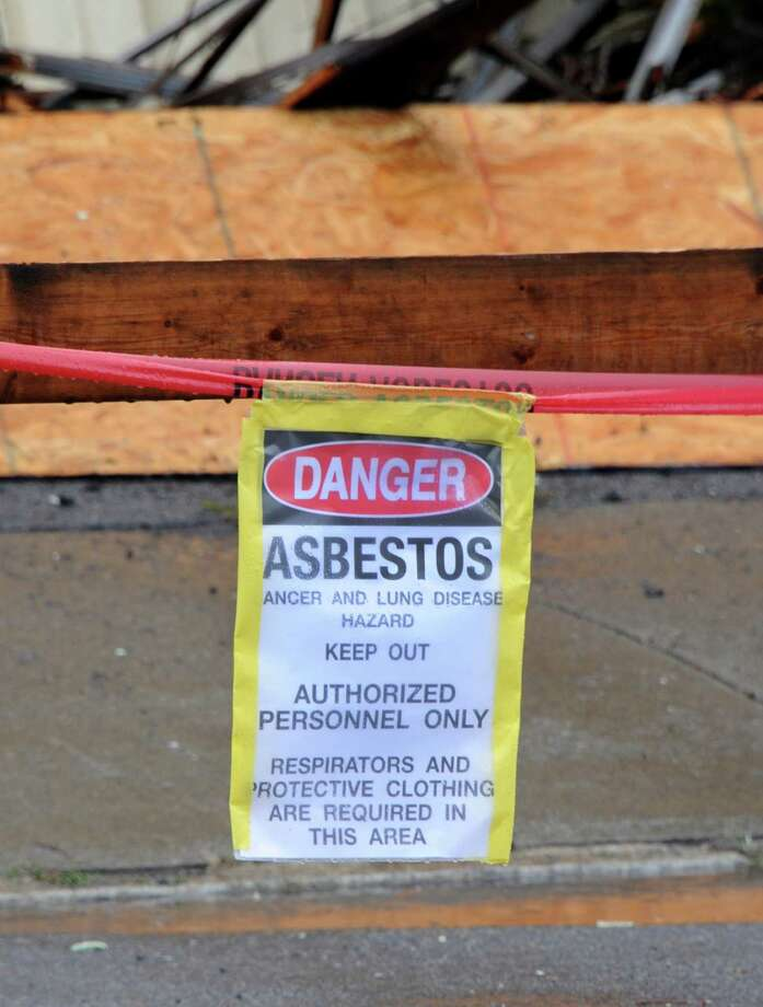 An asbestos sign is seen in front of a house at 2033 Broadway, the first of about 89 run-down homes to be demolished on Tuesday, Oct. 21, 2014 in Schenectady, N.Y. Sen. Charles Schumer joined Schenectady city officials for the demolition and helped the city get about $3 million to help with the cost of knocking down these structures. (Lori Van Buren / Times Union) Photo: Lori Van Buren / 00029128A