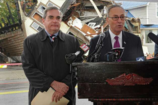 Sen. Charles Schumer joins Schenectady Mayor Gary McCarthy, left, and other city officials for the demolition of 2033 Broadway, the first of about 89 run-down homes in the municipality on Tuesday, Oct. 21, 2014 in Schenectady, N.Y. Schumer helped the city get about $3 million to help with the cost of knocking down these structures. (Lori Van Buren / Times Union) Photo: Lori Van Buren / 00029128A