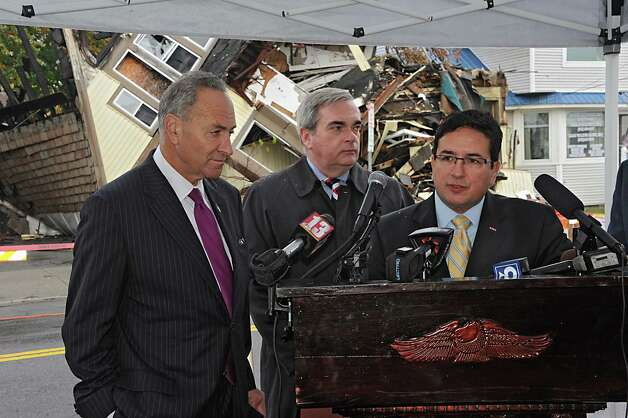 Sen. Charles Schumer, left,  joins Schenectady Mayor Gary McCarthy, center, and Jaime Forero, field office director U.S. Department of Housing and Urban Development, for the demolition of 2033 Broadway, the first of about 89 run-down homes in the municipality on Tuesday, Oct. 21, 2014 in Schenectady, N.Y. Schumer helped the city get about $3 million to help with the cost of knocking down these structures. (Lori Van Buren / Times Union) Photo: Lori Van Buren / 00029128A