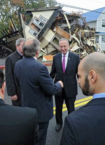 Sen. Charles Schumer, center, joins city officials for the demolition of 2033 Broadway, the first of about 89 run-down homes in the municipality on Tuesday, Oct. 21, 2014 in Schenectady, N.Y. Schumer helped the city get about $3 million to help with the cost of knocking down these structures. (Lori Van Buren / Times Union) Photo: Lori Van Buren / 00029128A