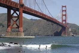 Two surfers ride a wave near Fort Point below the Golden Gate Bridge in this May 3, 2014 file photo in San Francisco.
