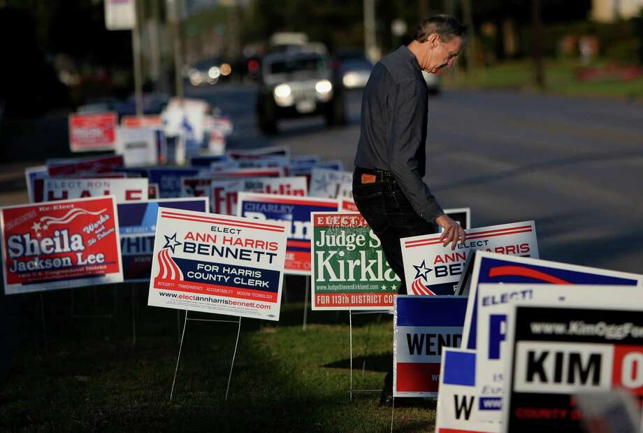 Robert Downs places yard signs for candidate Ann Harris Bennett at early voting at State Representative District 134M at the Metropolitan Multi Service Center on West Gray Monday, Oct. 20, 2014, in Houston, Texas. ( Gary Coronado / Houston Chronicle ) Photo: Gary Coronado, Staff / © 2014 Houston Chronicle