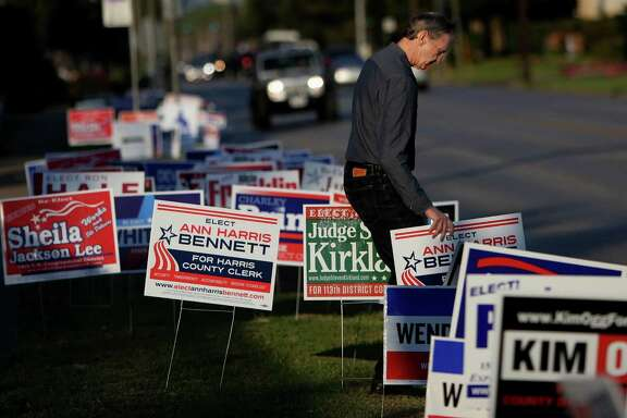Robert Downs places yard signs for candidate Ann Harris Bennett at early voting at State Representative District 134M at the Metropolitan Multi Service Center on West Gray Monday, Oct. 20, 2014, in Houston, Texas. ( Gary Coronado / Houston Chronicle )