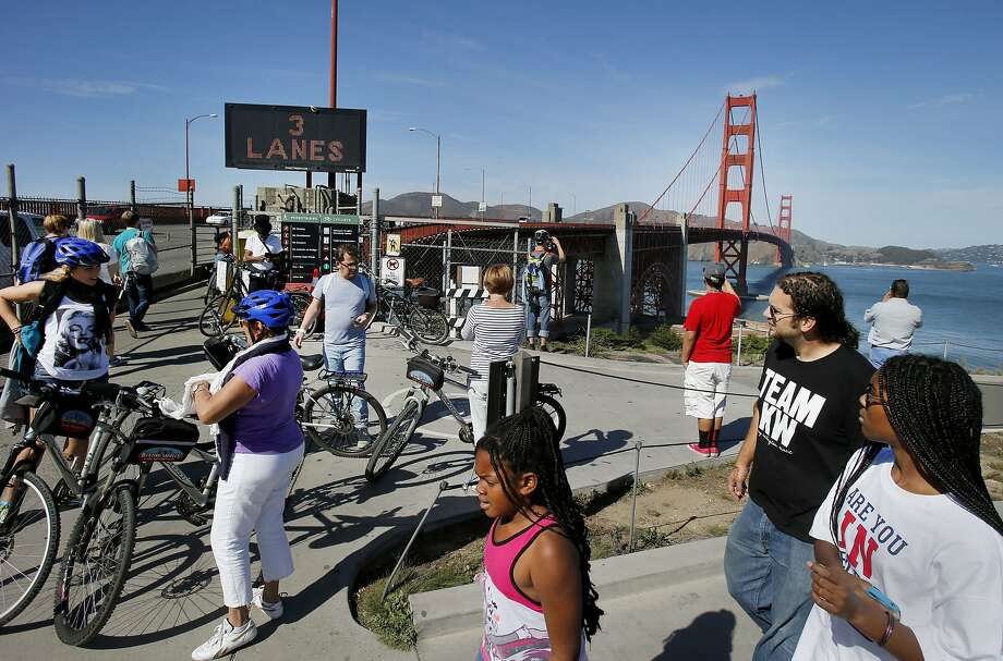 A crowd of pedestrians and cyclists prepare to walk on the east side of the Golden Gate Bridge Tuesday October 21, 2014. Officials at the Golden Gate Bridge are again considering charging tolls for pedestrians and cyclists. Photo: Brant Ward, The Chronicle