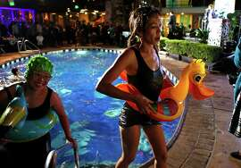 Nerd Wallet's Flo Thinh (right) exits the pool while taking part in the TNDC Celebrity Pool Toss at Phoenix Hotel in San Francisco, Calif. on Wednesday, October 8, 2014.