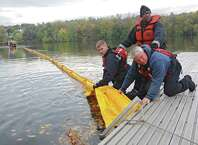 From left, members of the Albany Fire Department Jimmy McCarroll, Stephen McCauley and Joseph Dale tie up the boom as the New York State Department of Environmental Conservation (DEC) conducts a joint oil spill training exercise with Canadian Pacific (CP) railroad, and the Albany Fire Department on the Hudson River at the Port of Albany in Albany, N.Y.  (Lori Van Buren / Times Union)