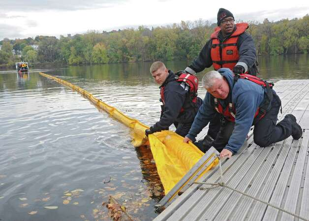 From left, members of the Albany Fire Department Jimmy McCarroll, Stephen McCauley and Joseph Dale tie up the boom as the New York State Department of Environmental Conservation (DEC) conducts a joint oil spill training exercise with Canadian Pacific (CP) railroad, and the Albany Fire Department on the Hudson River at the Port of Albany in Albany, N.Y.  (Lori Van Buren / Times Union) Photo: Lori Van Buren / 00029141A