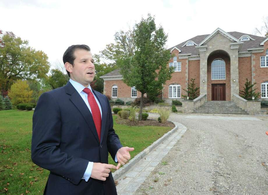 Sheldon Good & Company's Jonathan Cuticelli in front of 39 Bedford Road in Greenwich, Conn., Tuesday, Oct. 21, 2014. The home will be auctioned on Sunday, November 16, at the home's location. According to Cuticelli, the suggested opening bid for the 9,000 square foot property is $2.5 million. Photo: Bob Luckey / Greenwich Time