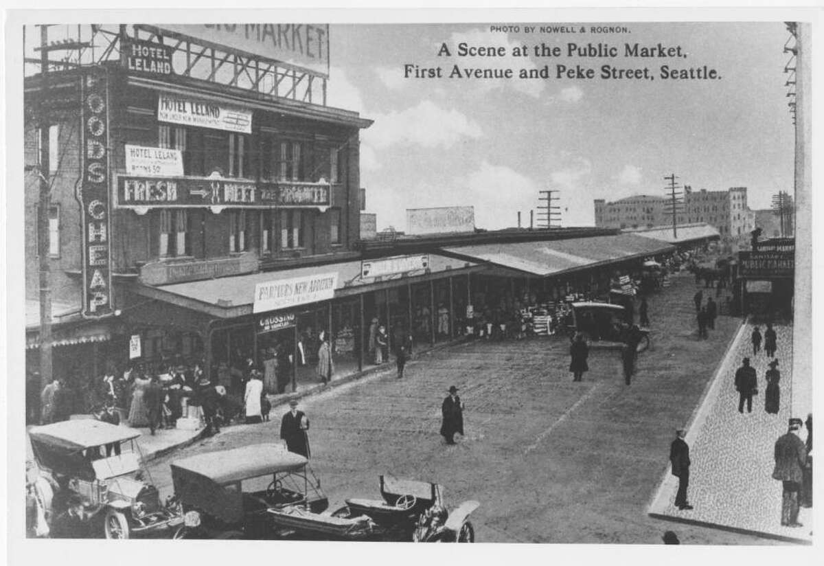 Photograph depicting Pike Place Market at the intersection of First Avenue and Pike Street. Hotel Leland can be seen on the left side of the image and a sign for the Sanitary Market can be seen on the right side. Taken between 1910 and 1919. spl_sh_00001