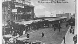 Photograph depicting Pike Place Market at the intersection of First Avenue and Pike Street. Hotel Leland can be seen on the left side of the image and a sign for the Sanitary Market can be seen on the right side. 1910-1919  spl_sh_00001