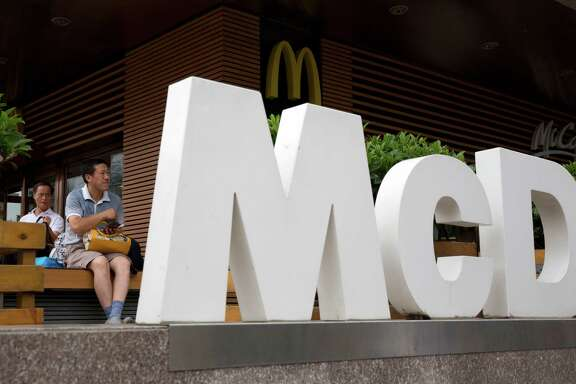 FILE - In this July 22, 2014 file photo, a man rests outside a McDonald's restaurant in Beijing. McDonald's reports quarterly financial results on Tuesday, Oct. 21, 2014. (AP Photo/Ng Han Guan, File)