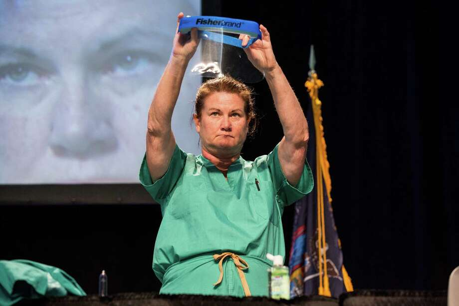 Barbara Smith, a nurse with Mount Sinai Health System, shows health care professionals how to properly put on protective medical gear Tuesday in a demonstration at the Jacob K. Javits Convention Center in New York City. Photo: Andrew Burton, Staff / 2014 Getty Images