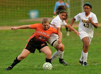 Stamford's Rachel Knight shields the ball from Trinity Catholic's Christina Bellacicco, center, and Tiara Starks, right, during their soccer game at Trinity Catholic High School in Stamford, Conn., on Tuesday, Oct. 21, 2014. Stamford won, 5-0.