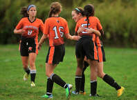 Stamford's Aissa Paul(5) embraces Bailey Bitetto as their team mates Mia Vitti(8) and Erica Stietzel(16) congragulate Bailey on her goal during their soccer game against Trinity Catholic at Trinity Catholic High School in Stamford, Conn., on Tuesday, Oct. 21, 2014. Stamford won, 5-0.