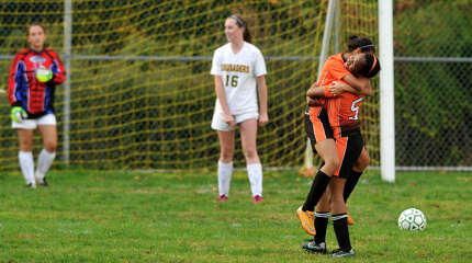 Stamford's Teresa Angon embraces her team mate Aissa Paul(5) after Paul scored a goal on Trinity Catholic goalie Amy Hurd, left, during their soccer game at Trinity Catholic High School in Stamford, Conn., on Tuesday, Oct. 21, 2014. Stamford won, 5-0.