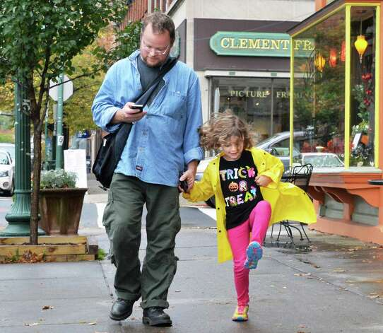 Six-year-old Cordelia Lauber of Valley Falls and her father Clinton Lauber make their way along Broadway after Cordelia's visit to her dentist Tuesday Oct. 21, 2014, in Troy, NY. (John Carl D'Annibale / Times Union) Photo: John Carl D'Annibale