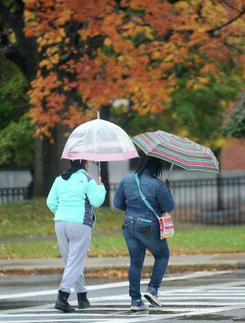 Two young women use umbrellas as they cross Veeder Ave. and State St. on Tuesday, Oct. 21, 2014 in Schenectady, N.Y. (Lori Van Buren / Times Union) Photo: Lori Van Buren