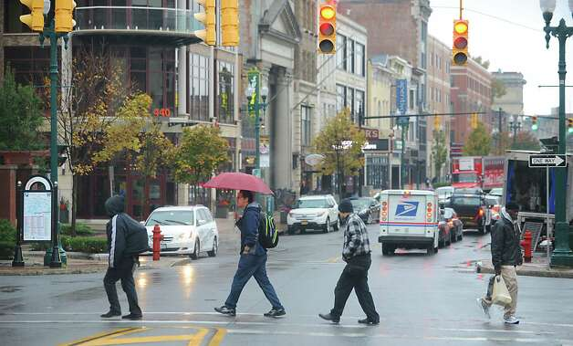 Pedestrians cross State St. on a rainy day Tuesday, Oct. 21, 2014 in Schenectady, N.Y. (Lori Van Buren / Times Union) Photo: Lori Van Buren