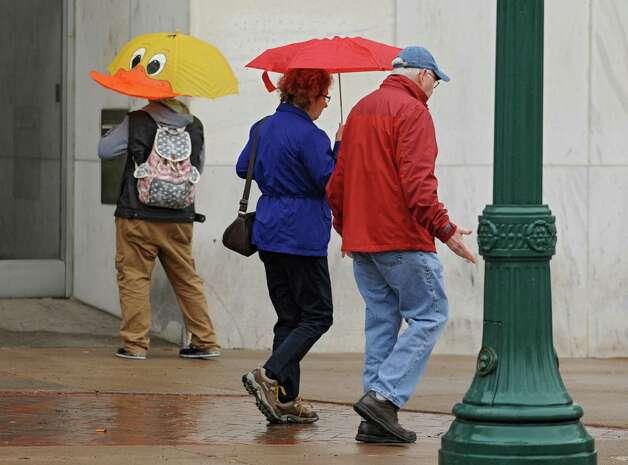 Pedestrians use umbrellas on State St. Tuesday, Oct. 21, 2014 in Schenectady, N.Y. (Lori Van Buren / Times Union) Photo: Lori Van Buren