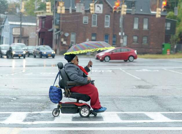 A woman uses an umbrella as she crosses Veeder Ave. and State St. on Tuesday, Oct. 21, 2014 in Schenectady, N.Y. (Lori Van Buren / Times Union) Photo: Lori Van Buren