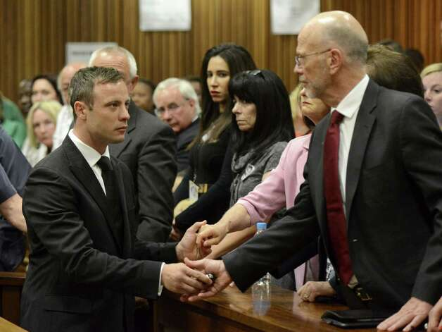 Oscar Pistorius, left, greets his uncle Arnold Pistorius, right, and other family members as he is led down to the cells of the court in Pretoria, South Africa, Tuesday, Oct. 21, 2014. Pistorius received a five-year prison sentence for culpable homicide by judge Thokozile Masipais for the killing of his girlfriend Reeva Steenkamp last year (AP Photo/Herman Verwey, Pool) ORG XMIT: XDF121 Photo: Herman Verwey / MEDIA 24 POOL