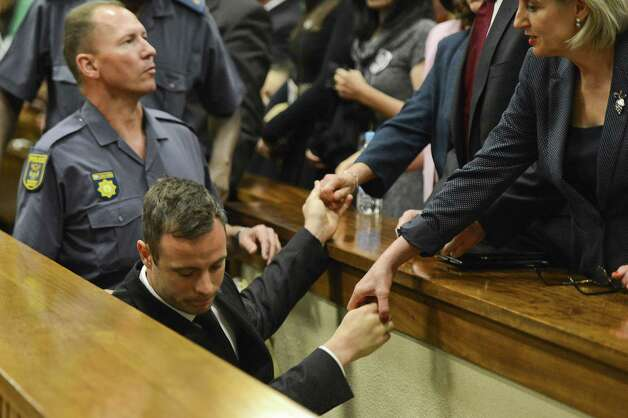 Oscar Pistorius, center,  touches hands with family members as he is led down to the cells of the court in Pretoria, South Africa, Tuesday, Oct. 21, 2014. Pistorius received a five-year prison sentence for culpable homicide by judge Thokozile Masipais for the killing of his girlfriend Reeva Steenkamp last year (AP Photo/Herman Verwey, Pool) ORG XMIT: XDF122 Photo: Herman Verwey / MEDIA 24 POOL