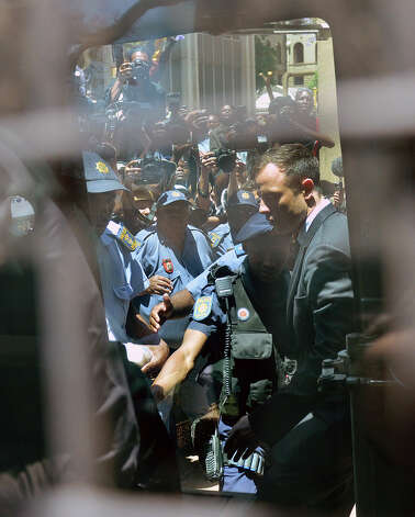 Oscar Pistorius, is led to an awaiting police vehicle to be take to prison outside the court in Pretoria, South Africa, Tuesday, Oct. 21, 2014. Pistorius was handed down a five-year sentence by judge Thokozile Masipais for killing his girlfriend Reeva Steenkamp last year.  (AP Photo/Antoine de Ras, Independent Newspapers)  SOUTH AFRICA OUT ORG XMIT: XDF828 Photo: Antoine De Ras / INDEPENDENT NEWSPAPERS