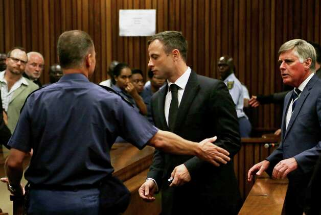 Oscar Pistorius, center, is led out of court in Pretoria, South Africa, Tuesday, Oct. 21, 2014.  Pistorius received a five-year prison sentence for culpable homicide by judge Thokozile Masipais for the killing of his girlfriend Reeva Steenkamp last year (AP Photo/Themba Hadebe) ORG XMIT: XDF114 Photo: Themba Hadebe / AP POOL