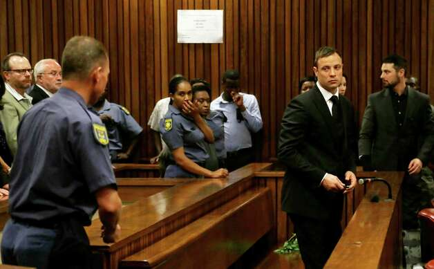 Oscar Pistorius, right, prepares to be led out of court in Pretoria, South Africa, Tuesday, Oct. 21, 2014. Pistorius received a five-year prison sentence for culpable homicide by judge Thokozile Masipais for the killing of his girlfriend Reeva Steenkamp last year (AP Photo/Themba Hadebe, Pool) ORG XMIT: XDF119 Photo: Themba Hadebe / AP POOL