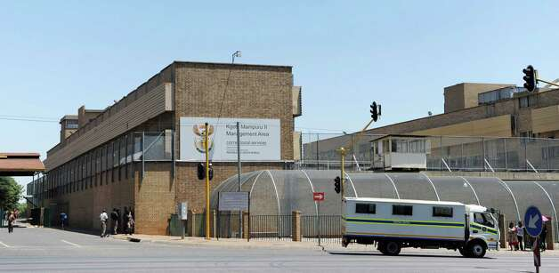 people walk outside the Kgosi Mampuru Correctional Services prison in Pretoria, South Africa, Tuesday, Oct. 21, 2014. Oscar Pistorius was sentenced to five years imprisonment at the facility by judge Thokozile Masipais for killing his girlfriend Reeva Steenkamp last year. (AP Photo) ORG XMIT: XDF142 / AP