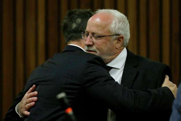 Oscar Pistorius is hugged by his estranged father, Henke Pistorius, right, as he arrives in court in Pretoria, South Africa, Tuesday, Oct. 21, 2014. Pistorius will finally learn his fate  when judge Thokozile Masipais is expected to announce the Olympic runner's sentence for killing girlfriend Reeva Steenkamp  (AP Photo/Themba Hadebe, Pool) ORG XMIT: XDF106 Photo: Themba Hadebe / AP POOL