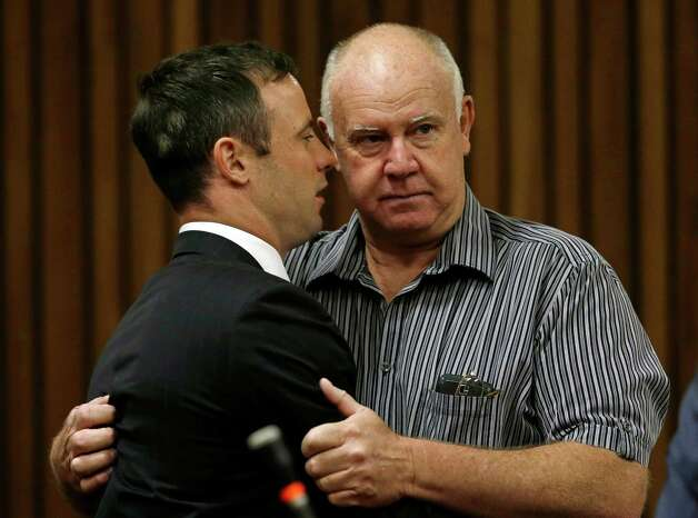 Oscar Pistorius is hugged by his coach Ampie Louw, right, at a court in Pretoria, South Africa, Tuesday, Oct. 21, 2014. Pistorius was sentenced to five years imprisonment by judge Thokozile Masipais for killing his girlfriend Reeva Steenkamp last year. (AP Photo/Themba Hadebe, Pool) ORG XMIT: XDF139 Photo: Themba Hadebe / AP POOL