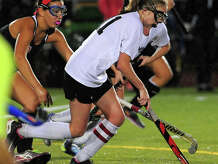 Trumbull's Emily Uus drives the ball ahead of Fairfield Warde's Becca Mitri, during girls field hockey action in Trumbull, Conn., on Tuesday October 21, 2014.