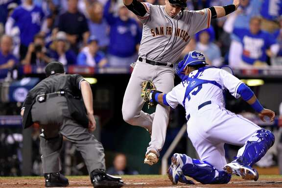 The San Francisco Giants' Buster Posey is tagged out at home by Kansas City Royals catcher Salvador Perez, right, in the first inning in Game 1 of the World Series on Tuesday, Oct. 21, 2014, at Kauffman Stadium in Kansas City, Mo. (John Sleezer/Kansas City Star/MCT)